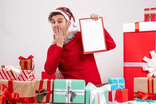 Vorderansicht junger mann, der hand an seinen mund setzt, der um weihnachtsgeschenke sitzt Kostenlose Fotos