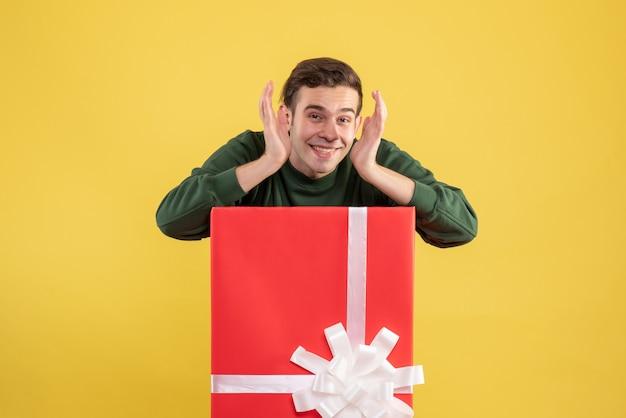 Vorderansicht junger mann, der hinter großer geschenkbox auf gelb steht Kostenlose Fotos