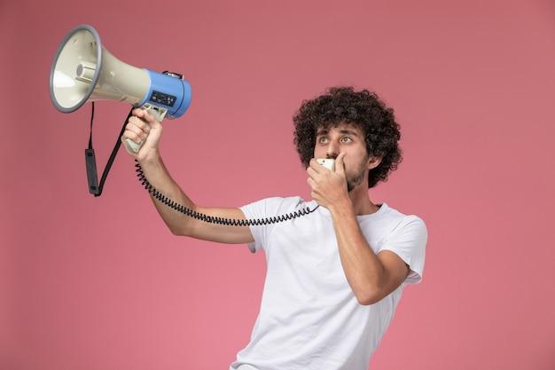 Vorderansicht junger mann, der leute mit handmikrofon informiert Kostenlose Fotos