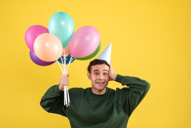 Vorderansicht junger mann mit grünem pullover, der ballons hält, die auf gelb stehen Kostenlose Fotos