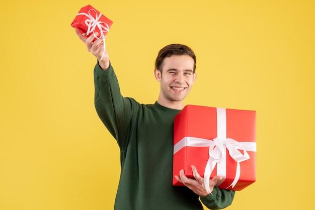Vorderansicht junger mann mit grünem pullover, der große und kleine geschenke hält, die auf gelb stehen Kostenlose Fotos