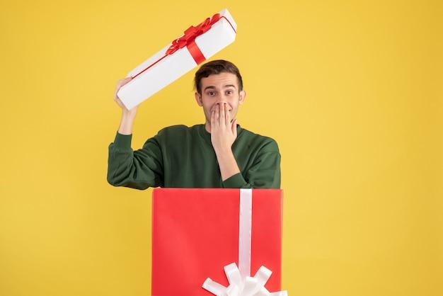 Vorderansicht junger mann mit kastenabdeckung, die hand an seinen mund setzt, der hinter großer geschenkbox auf gelb steht Kostenlose Fotos