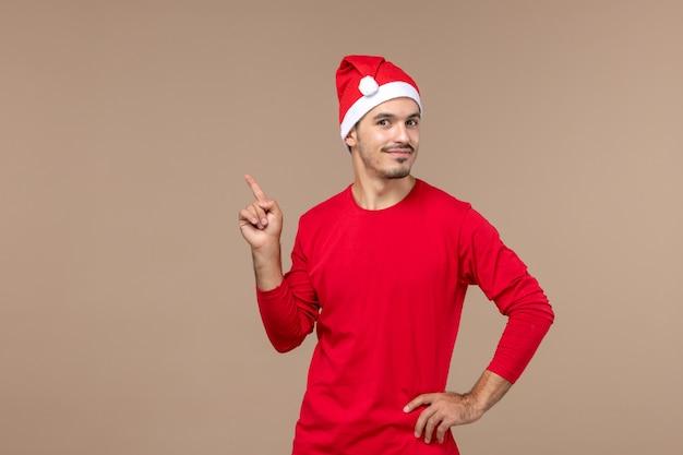 Vorderansicht junger mann mit lächelndem ausdruck auf männlicher emotionsfeiertagsfarbe des braunen hintergrunds Kostenlose Fotos
