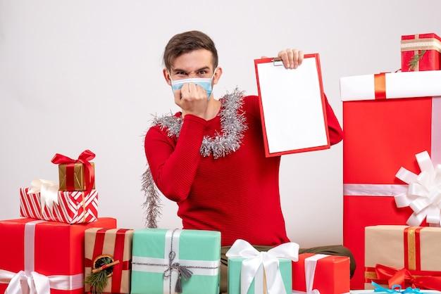 Vorderansicht junger mann mit maske, die hand an seinen mund setzt, der um weihnachtsgeschenke sitzt Kostenlose Fotos