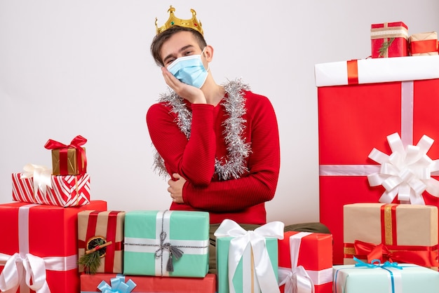Vorderansicht junger mann mit maske, die hand auf seine wange setzt, die auf bodenweihnachtsgeschenken sitzt Kostenlose Fotos