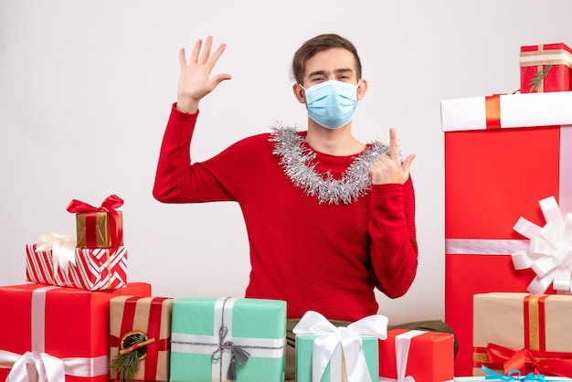 Vorderansicht junger mann mit maske, die seine hand aufstellt, die um weihnachtsgeschenke sitzt Kostenlose Fotos