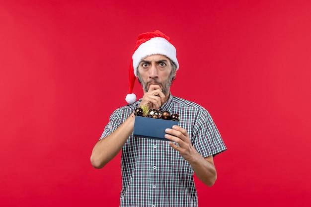 Vorderansicht junger mann mit weihnachtsbaumspielzeug auf rotem schreibtisch Kostenlose Fotos