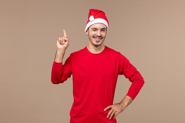 Vorderansicht junger mann zwinkert und lächelt auf braunem hintergrund männliche farbemotionsfeiertag Kostenlose Fotos