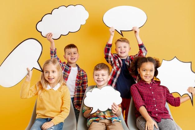 Vorderansicht kinder, die chatblasen halten Premium Fotos