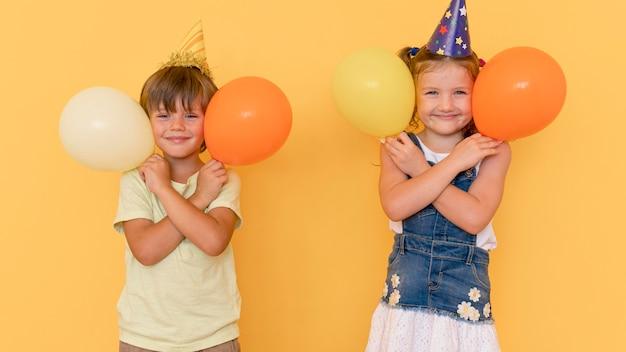 Vorderansicht kinder, die mit luftballons spielen Kostenlose Fotos