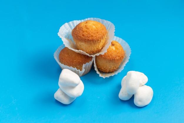 Vorderansicht kleine köstliche kuchen lokalisiert auf blauem hintergrund Kostenlose Fotos