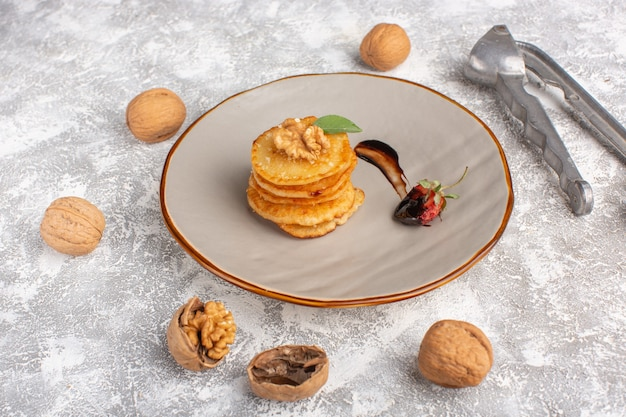 Vorderansicht kleines keksgebäck mit walnüssen auf dem leuchttisch, kuchenkekszucker süßes gebäck backen Kostenlose Fotos