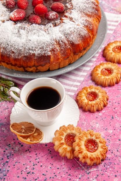 Vorderansicht köstlicher erdbeerkuchenzucker pulverisiert mit keksen und tee auf dem rosa oberflächenkuchen süßer zuckerkeksplätzchentee Kostenlose Fotos