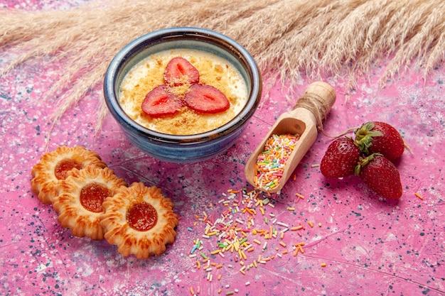 Vorderansicht köstliches cremiges dessert mit rot geschnittenen erdbeeren und kleinen keksen auf hellrosa wanddessert eisbeerencreme süße frucht Kostenlose Fotos