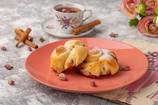 Vorderansicht köstliches gebäck mit füllung innenplatte zusammen mit tee und zimt auf dem weißen tisch, süßer zuckerkuchen backen gebäck Kostenlose Fotos