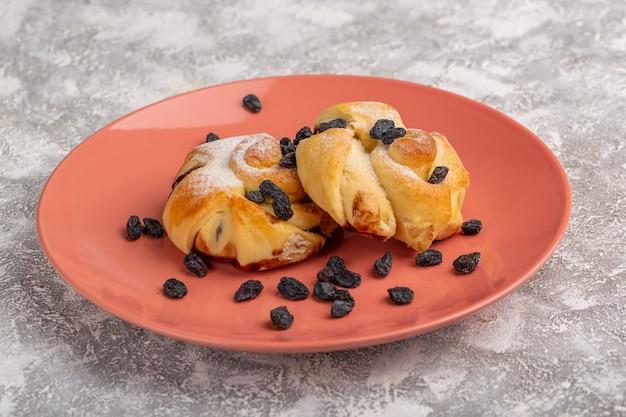 Vorderansicht köstliches gebäck mit füllung innerhalb platte zusammen mit getrockneten früchten auf weißem tisch, süßer zuckerkuchen backen gebäck Kostenlose Fotos