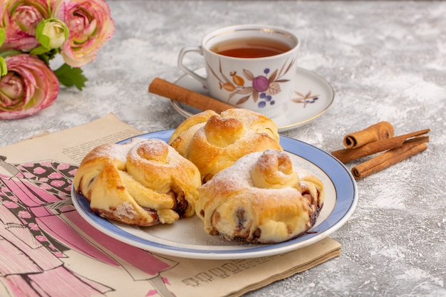 Vorderansicht köstliches gebäck mit füllung innerhalb platte zusammen mit tee und zimt auf weißem tisch, süßer zuckerkuchen backen gebäckfrucht Kostenlose Fotos