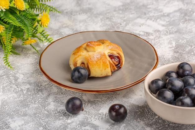 Vorderansicht köstliches gebäck mit füllung zusammen mit schwarzdorn auf dem leuchttisch, süßer zuckerkuchen backen gebäckfrucht Kostenlose Fotos