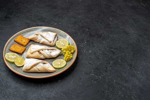 Vorderansicht köstliches teiggebäck süß und zucker pulverisiert auf dunkelgrauer wand süßes kuchenteiggebäck backen zuckerkuchenplätzchen Kostenlose Fotos