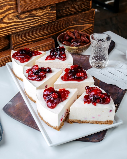 Vorderansicht kuchen schneidet leckere kirschkuchen in weißer platte auf dem hellen boden Kostenlose Fotos