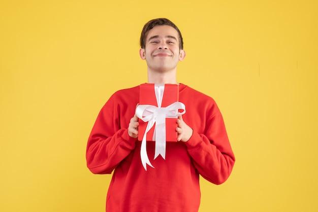 Vorderansicht lächelte junger mann, der auf gelb steht Kostenlose Fotos