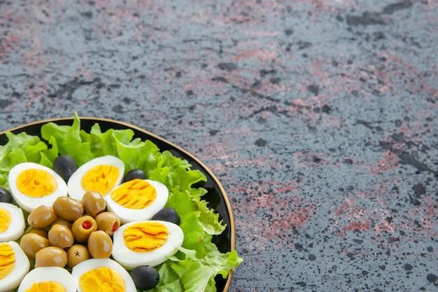 Vorderansicht leckerer eiersalat besteht aus grünem salat und oliven auf hellem hintergrund Kostenlose Fotos