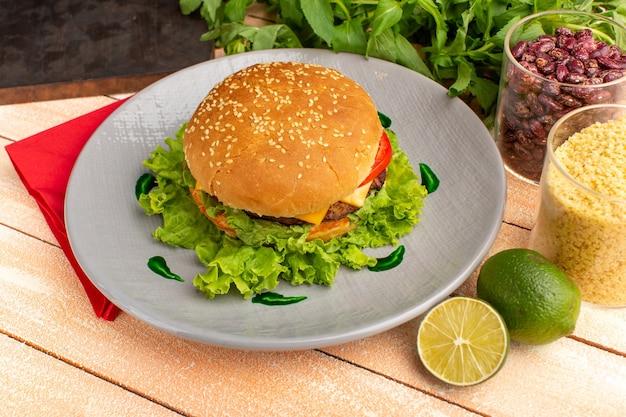Vorderansicht leckeres hühnchensandwich mit grünem salat und gemüse innerhalb platte auf dem hölzernen sahne-schreibtisch. Kostenlose Fotos
