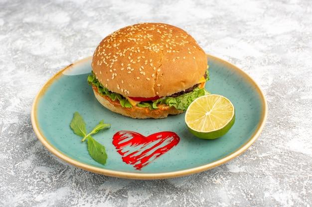 Vorderansicht leckeres hühnchensandwich mit grünem salat und gemüse innerhalb platte mit zitrone auf weißem schreibtisch. Kostenlose Fotos