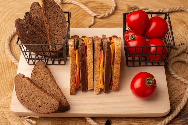 Vorderansicht leckeres toastsandwich mit käseschinken zusammen mit brotlaibs der roten tomaten auf holzschreibtisch Kostenlose Fotos