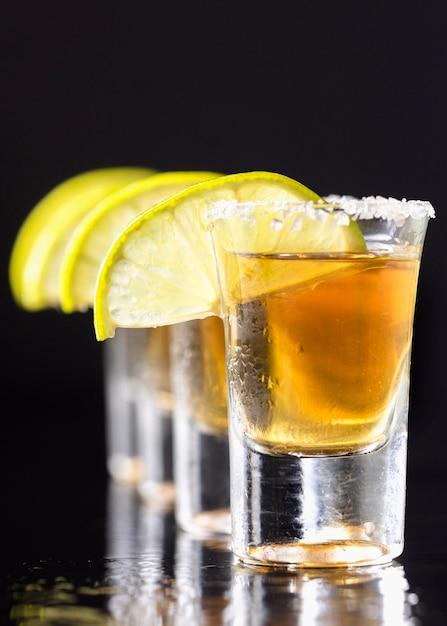 Vorderansicht linie von goldenen tequila-aufnahmen mit limettenscheiben Kostenlose Fotos