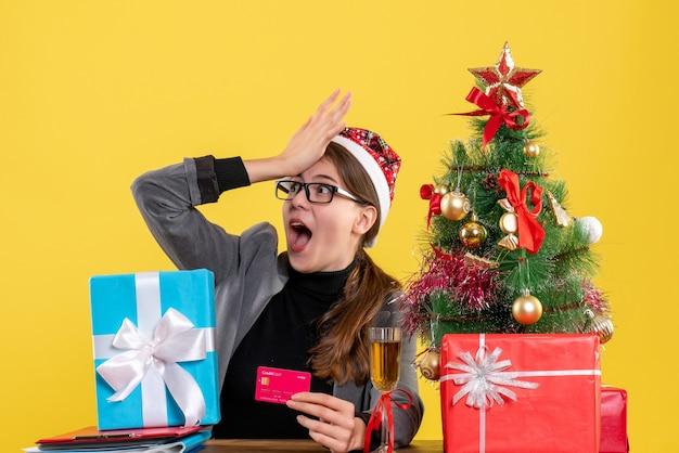 Vorderansicht-mädchen mit großen augen und weihnachtsmütze, die am tisch sitzen und hand setzen Kostenlose Fotos