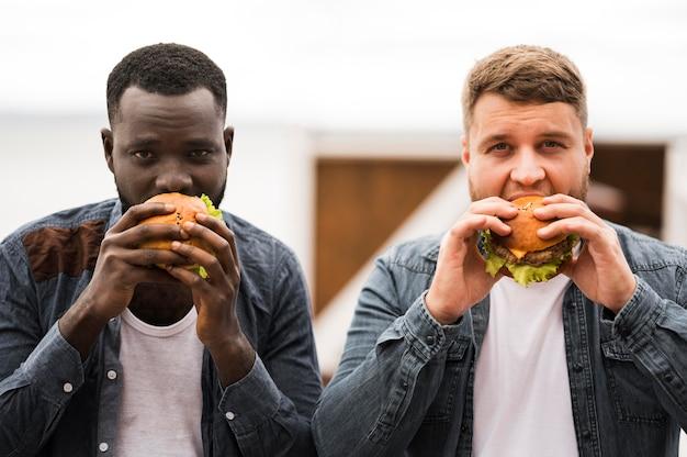 Vorderansicht männer, die burger zusammen essen Kostenlose Fotos