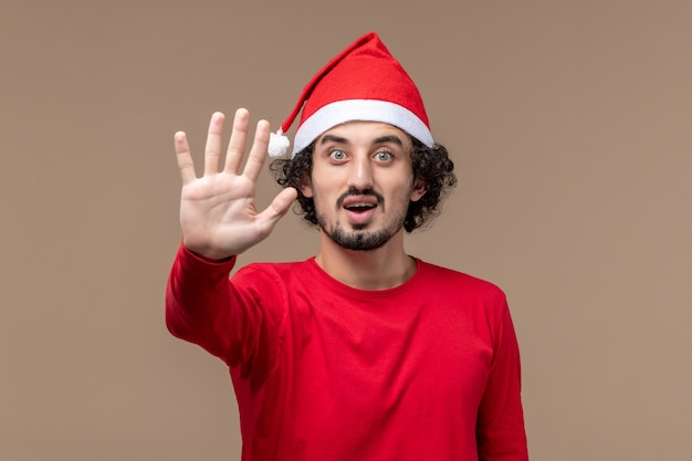 Vorderansicht männlich in rot, das die zahl auf den weihnachtsfeiertagsemotionsweihnachtsbraun zeigt Kostenlose Fotos
