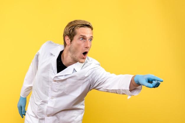 Vorderansicht männlicher arzt überrascht auf gelbem hintergrund sanitäter covid-krankenhaus mensch Kostenlose Fotos