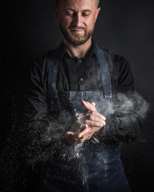 Vorderansicht mann mit mehl vom brot auf seinen händen Kostenlose Fotos