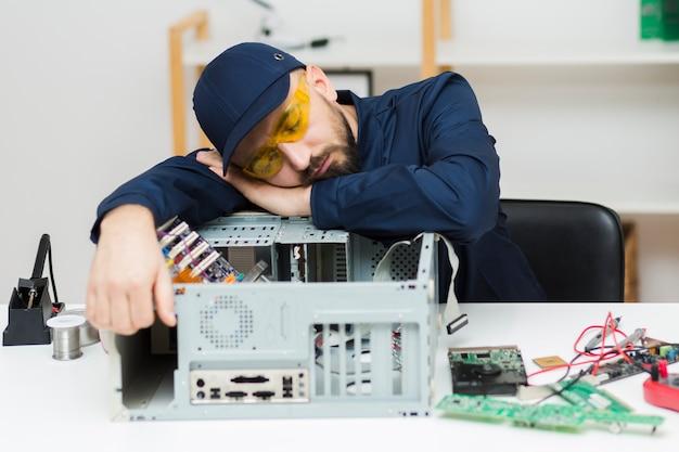 Vorderansicht mann schlafend beim reparieren eines computers Kostenlose Fotos