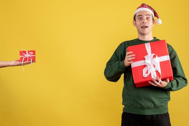 Vorderansicht mit großen augen junger mann, der weihnachtsgeschenk das geschenk in der weiblichen hand auf gelb hält Kostenlose Fotos