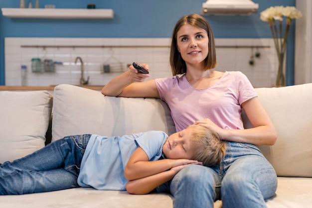 Vorderansicht mutter beim fernsehen, während sohn schläft