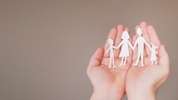Vorderansicht person, die in händen niedliche papierfamilie mit kopienraum hält Kostenlose Fotos
