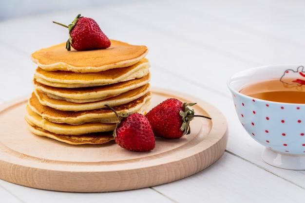Vorderansicht pfannkuchen mit erdbeeren auf einem tablett mit einer tasse tee Kostenlose Fotos