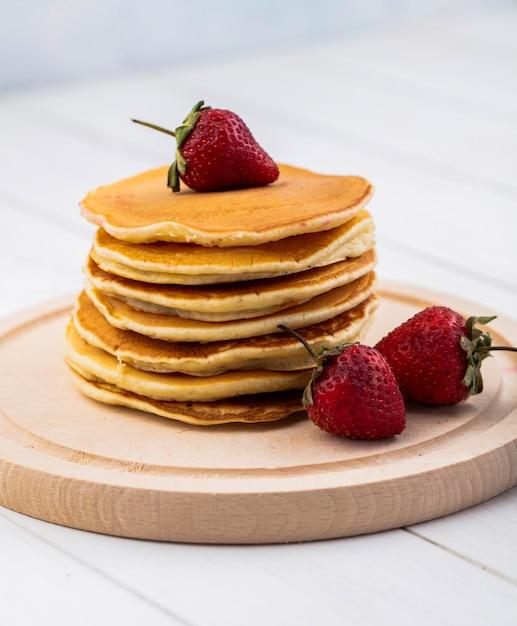 Vorderansicht pfannkuchen mit erdbeeren auf einem tablett Kostenlose Fotos