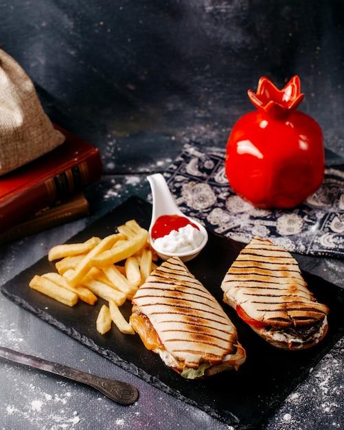 Vorderansicht pommes frites mit geschnittenem sandwich in schwarzer platte auf dem grauen schreibtisch Kostenlose Fotos