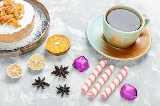 Vorderansicht runder kleiner kuchenzucker pulverisiert mit rosinentee und bonbons auf weißer oberfläche zucker süßer keks sahne-teekuchen Kostenlose Fotos