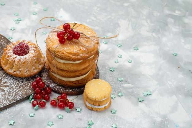 Vorderansicht-sandwichkekse gebunden mit sahnefüllung zusammen mit kuchen auf dem dunklen schreibtisch Kostenlose Fotos