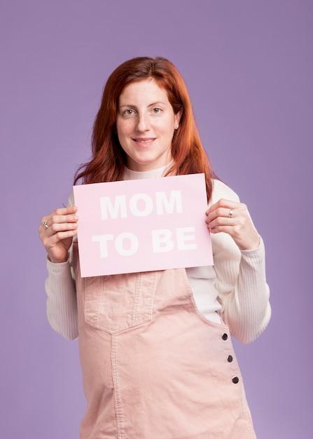 Vorderansicht schwangere frau, die papier mit mutter hält, um nachricht zu sein Kostenlose Fotos