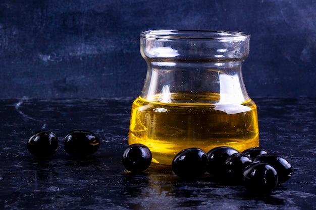Vorderansicht schwarze oliven mit olivenöl in einem glas auf schwarz Kostenlose Fotos