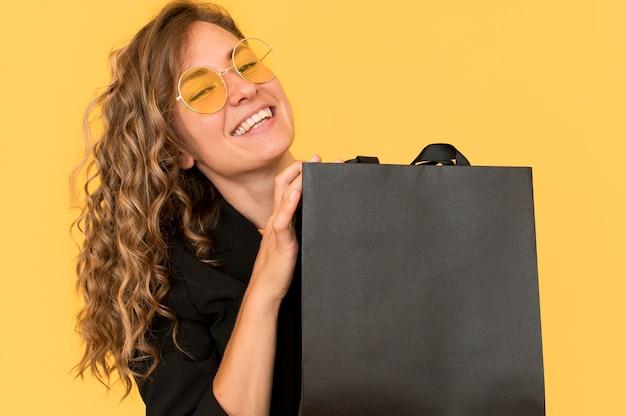 Vorderansicht smiley-frau und schwarze einkaufstasche Kostenlose Fotos
