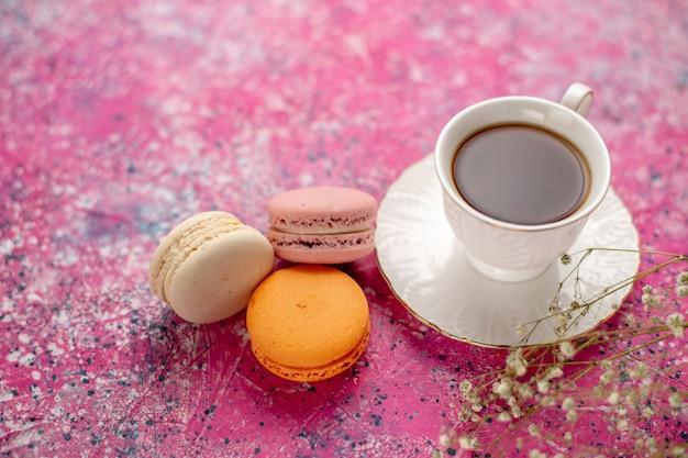 Vorderansicht tasse tee in tasse auf teller mit französischen macarons auf dem rosa schreibtisch Kostenlose Fotos