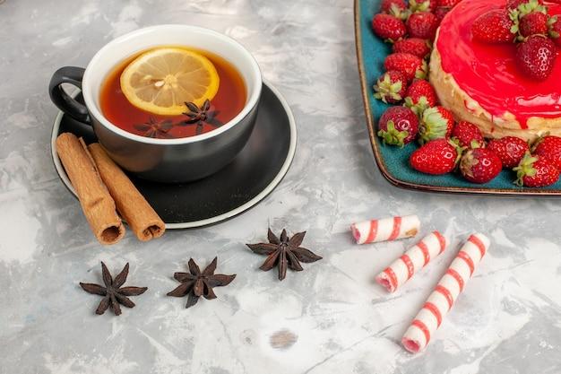 Vorderansicht tasse tee mit zimt und wenig erdbeerkuchen auf weißer oberfläche Kostenlose Fotos