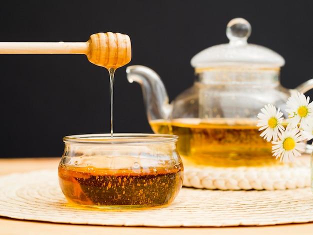 Vorderansicht teekanne und honigschöpflöffel über glas Kostenlose Fotos